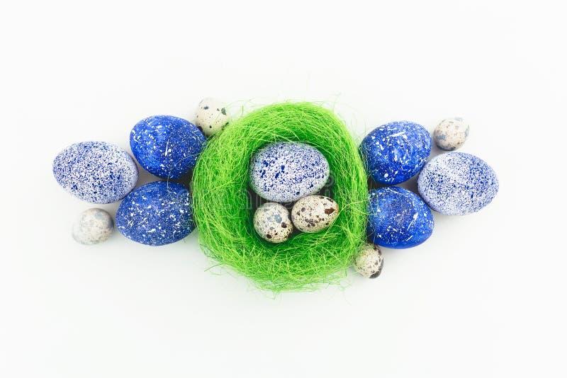 蓝色有斑点的复活节彩蛋和鹌鹑蛋在白色背景隔绝的巢 平的位置,顶视图 愉快的复活节 图库摄影