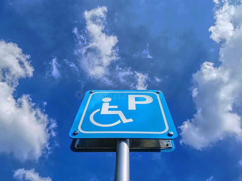 蓝色有残障的停放的标志低角度视图反对蓝色多云天空的 免版税库存图片