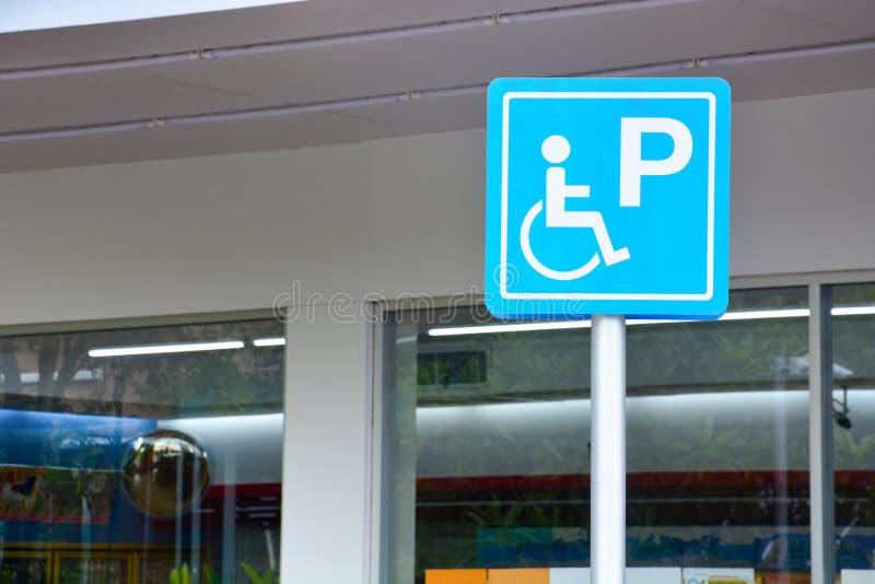 蓝色有残障的标志标记停车位,在杆的残疾停放的许可证标志与加油站的便利店 免版税库存照片