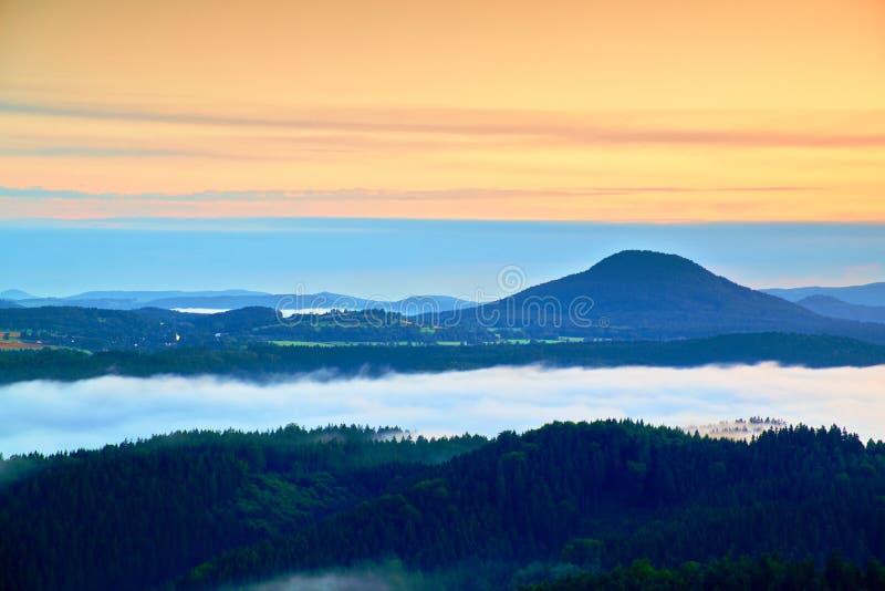 蓝色有雾的深谷在多雨夜以后 岩石小山轰鸣声观点 雾移动在树之间小山和峰顶,蓝色 图库摄影