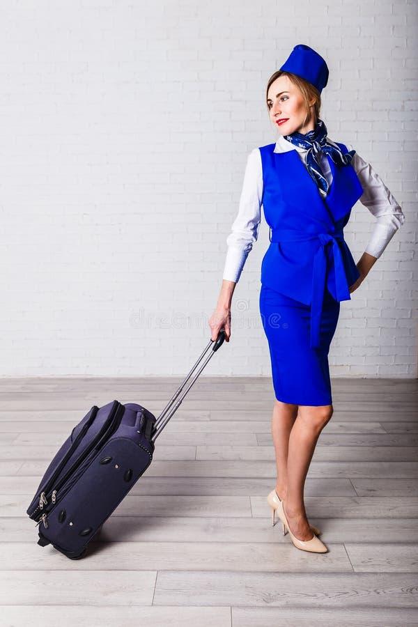 蓝色服装的空中小姐带着手提箱 免版税库存照片