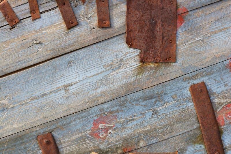 蓝色木板和生锈的金属条纹作为葡萄酒背景 库存照片