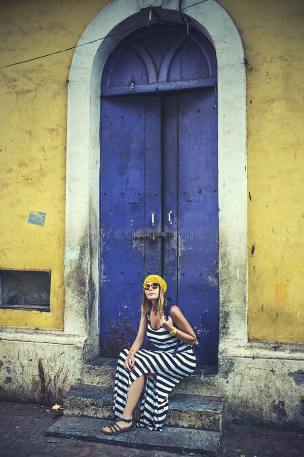 蓝色木门背景的年轻美丽的愉快的妇女  免版税库存照片