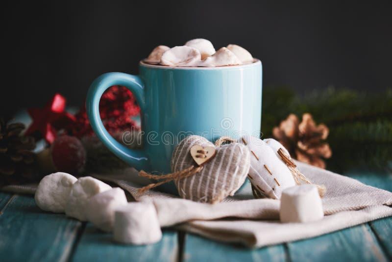 蓝色杯子用热巧克力和蛋白软糖填装了 库存照片