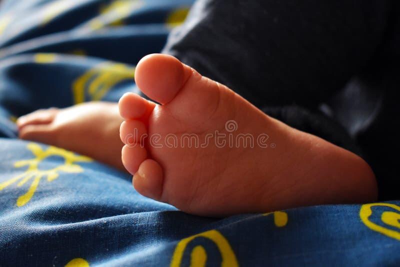 蓝色板料的赤足睡觉的婴孩与黄色太阳 免版税库存图片