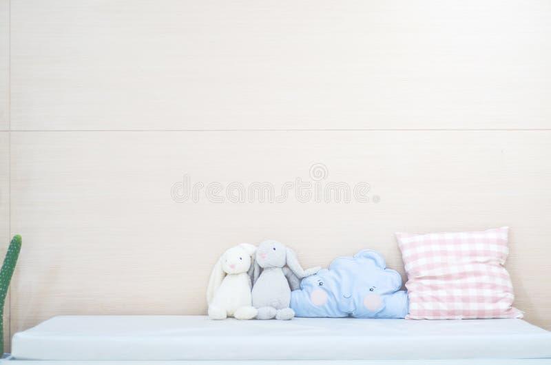 蓝色枕头,逗人喜爱的兔子玩偶在床上在卧室 库存照片