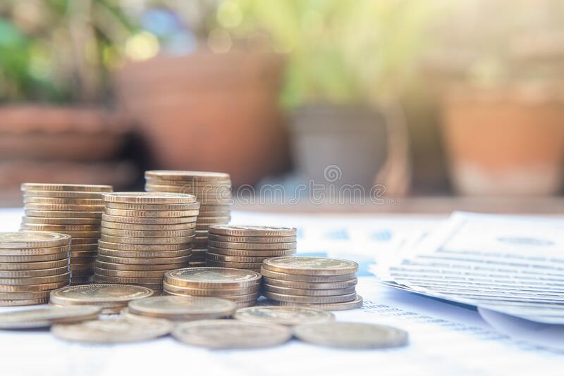 蓝色柔和图纸上的一叠硬币,以及带有太阳光的模糊自然背景 商业、财务、市场营销、电子商务c 库存照片