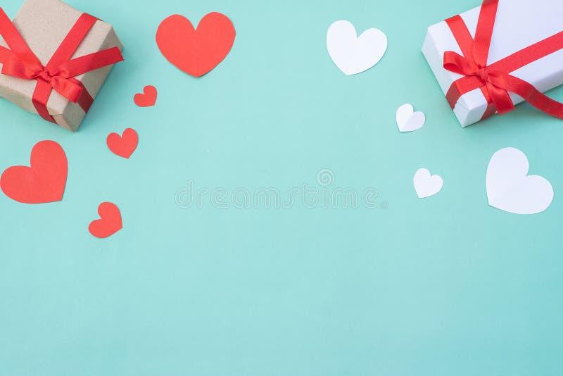 蓝色柔和背景上的红白心礼盒 情人节或婚礼的概念与设计 免版税库存照片