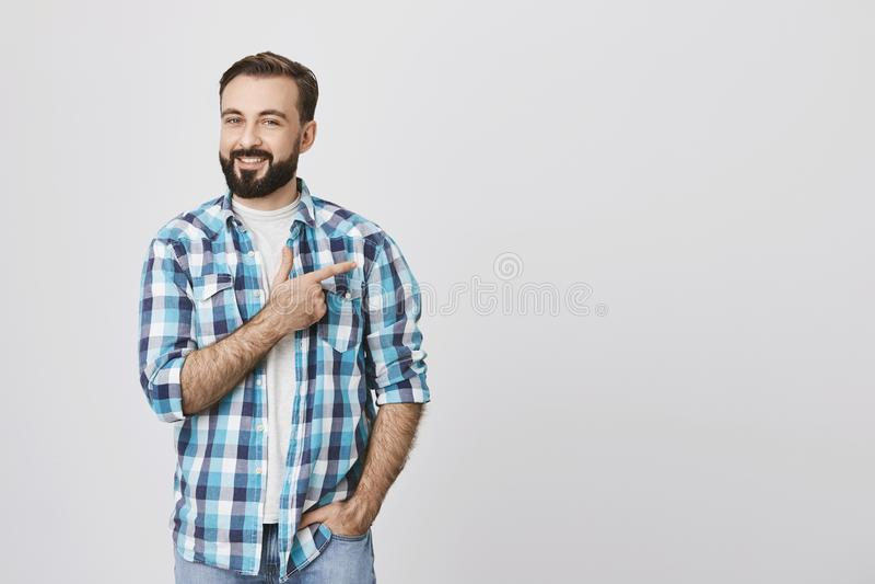 蓝色格子花呢上衣的迷人的有胡子的成人人指向与食指的,当在口袋的另一只手,在灰色时 图库摄影