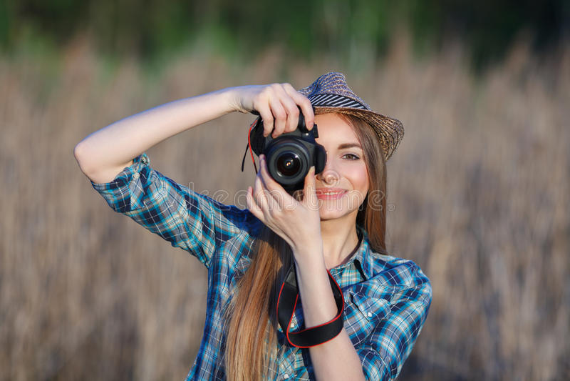 蓝色格子花呢上衣草帽的可爱的年轻白肤金发的妇女享受她的时间的拍在草甸的照片户外 免版税库存照片