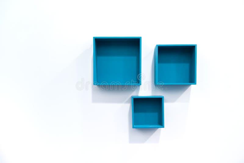 蓝色框在墙壁上搁置 免版税库存照片