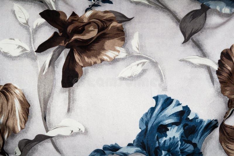 蓝色棕色花的安排在织品背景的 免版税库存照片