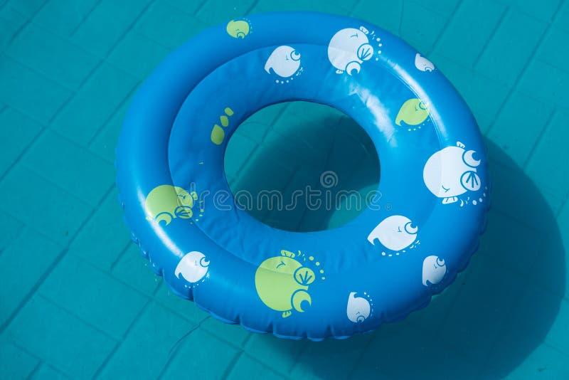蓝色橡胶环在水池在庭院里 夏天的概念 库存照片