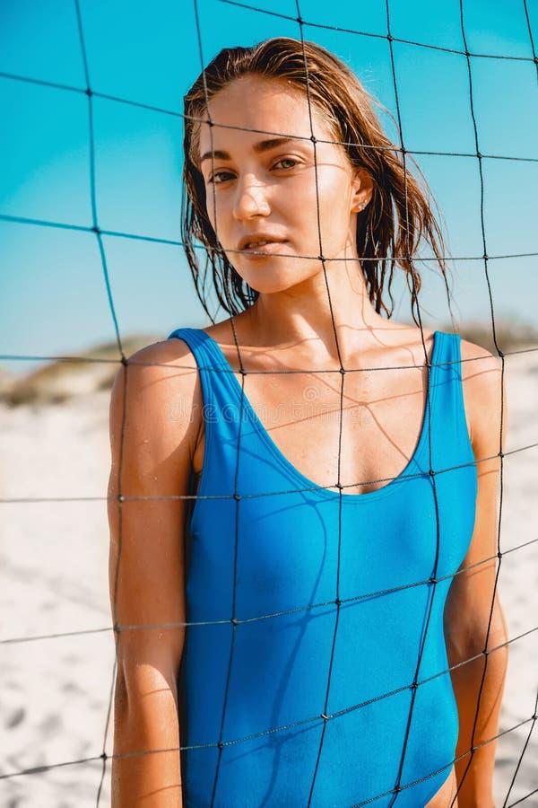 蓝色比基尼泳装的可爱的少妇有在沙滩的网球网的 库存照片