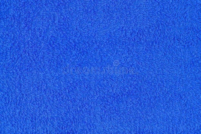 蓝色毛巾纹理 毛巾两端有绒穗之布的特写镜头 免版税图库摄影