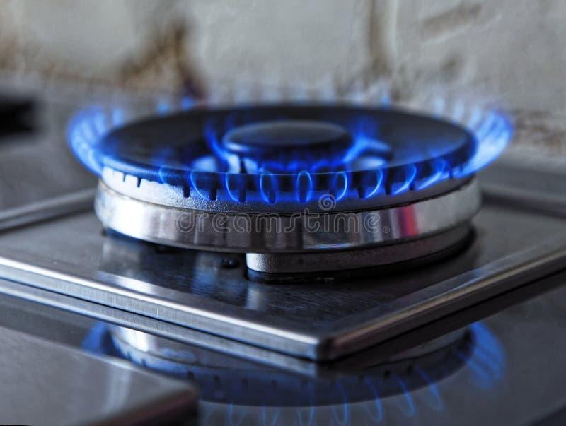蓝色气体火焰  关闭从厨房煤气炉的灼烧的火圆环 全景 免版税库存照片