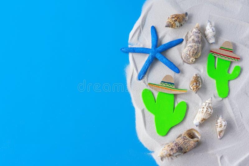 蓝色沙质背景中带墨西哥仙人掌和索姆布雷罗帽的Cinco de Mayo 美国嘉年华,墨西哥假日,暑假 库存照片