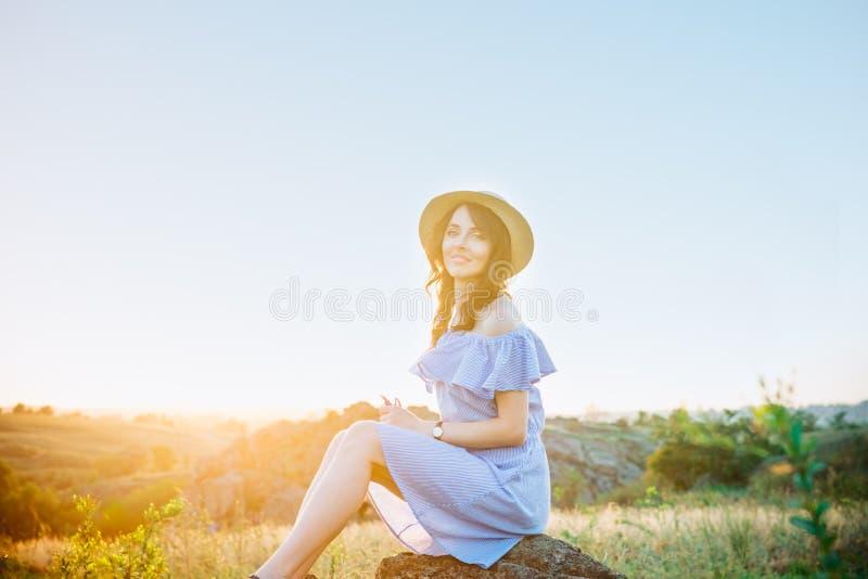 蓝色浪漫礼服和草帽的在太阳光享受在自然的年轻女人画象夏天日落 安静和和谐 免版税库存图片