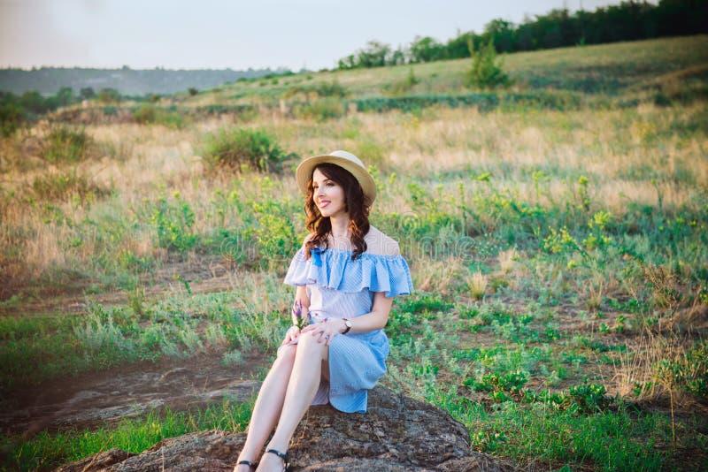 蓝色浪漫礼服和草帽的在绿色草甸享受夏天日落的年轻轻松的白种人妇女画象  镇静和 免版税库存照片