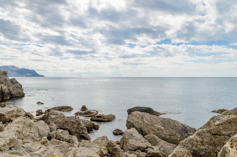 蓝色海、锋利的岩石和云彩 图库摄影