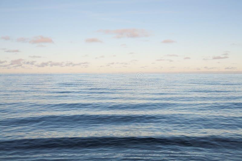 蓝色海和安静挥动在日落 库存图片