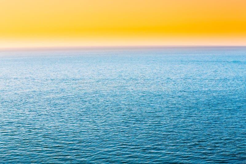 蓝色海或海洋和黄色清楚的日落或日出天空背景 库存照片