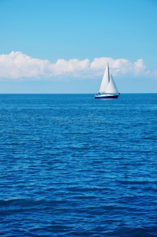 蓝色海水和一条白色风船 库存照片