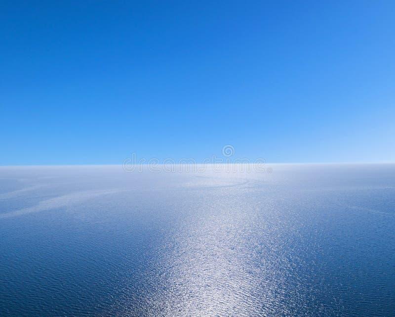 蓝色海水背景和太阳反射的鸟瞰图 空中飞行寄生虫视图 波浪水在晴朗的tro的表面纹理 免版税库存照片