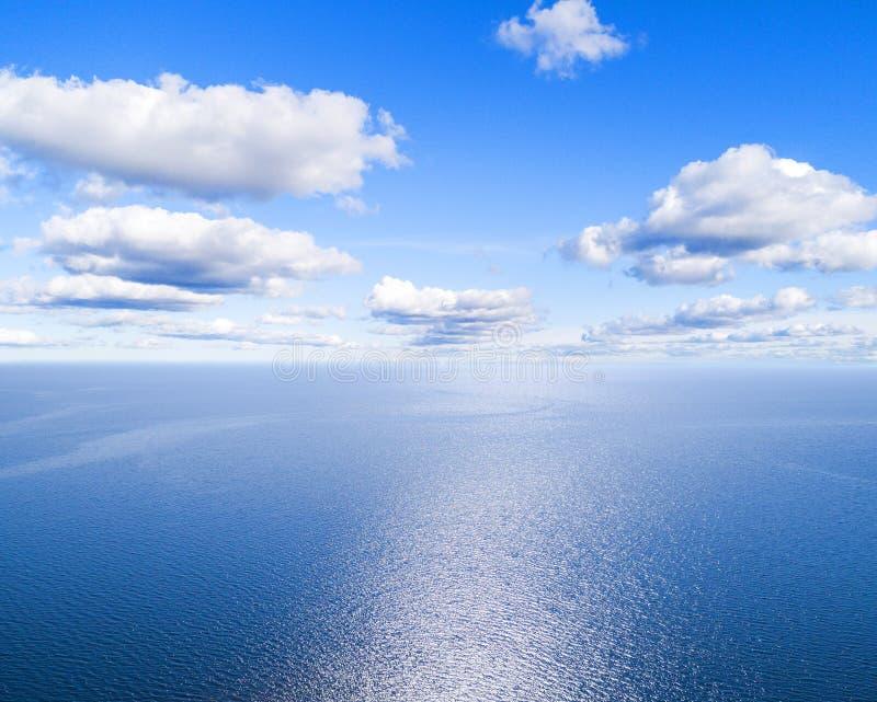 蓝色海水背景和太阳反射的鸟瞰图 空中飞行寄生虫视图 波浪水在晴朗的tro的表面纹理 免版税库存图片