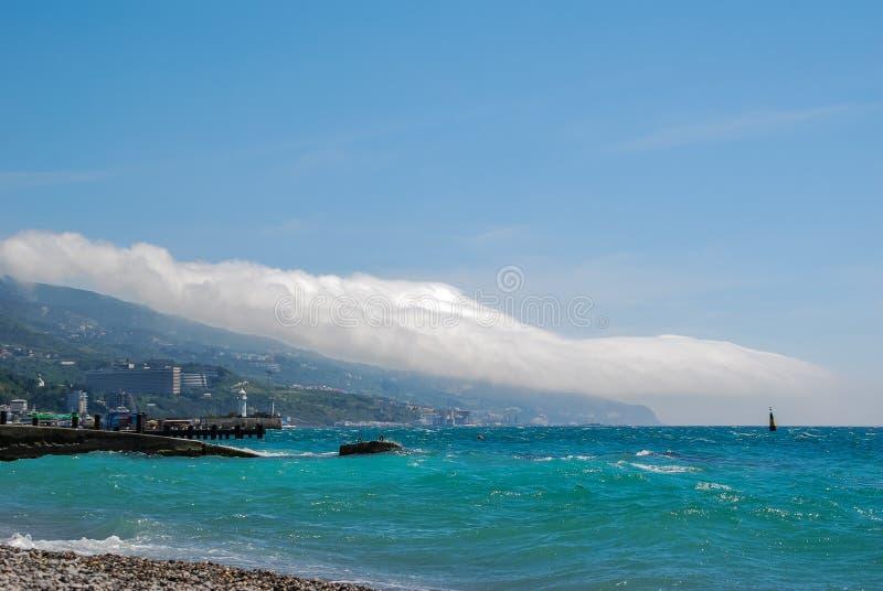 蓝色海,云彩审阅山的银行的 库存图片