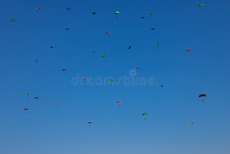 蓝色清楚的天空的许多小伞兵与在skydiving的多彩多姿的降伞与下来极端飞行期间 adria 库存图片