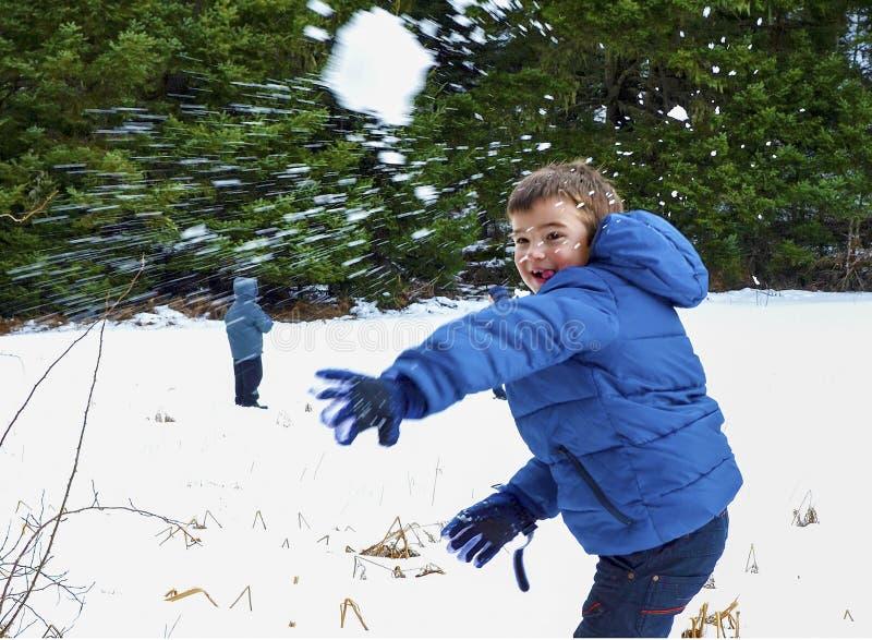 蓝色温暖的外套的男孩获得乐趣在有雪球的美好的冬天地方 免版税图库摄影