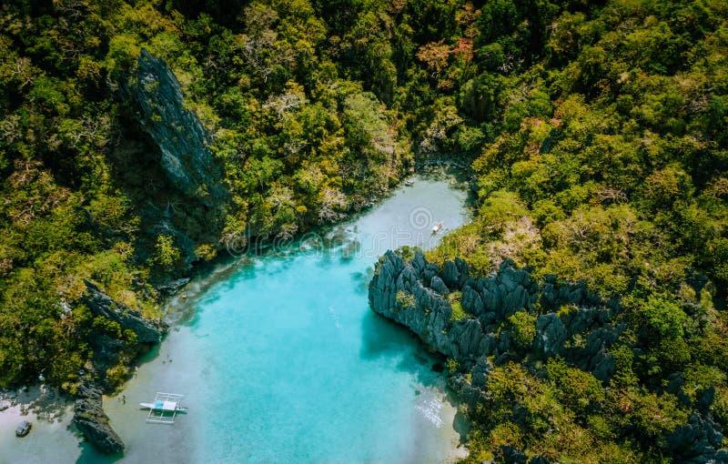 蓝色热带海岛绿松石透明盐水湖水空中寄生虫视图有坚固性陡峭的山岩石的 库存照片