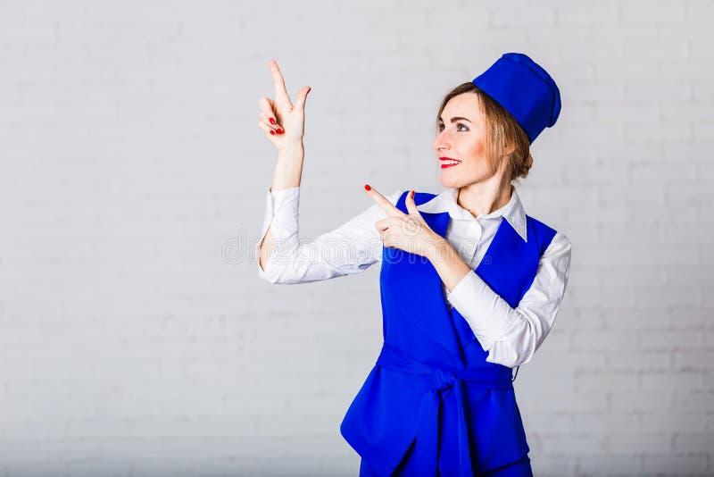 蓝色焰晕的一位快乐的空中小姐做姿态用她的手 库存图片