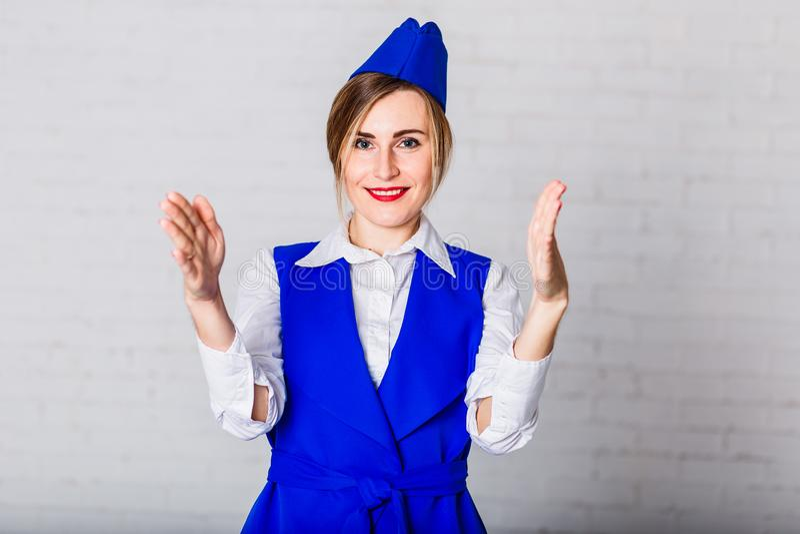 蓝色焰晕的一位快乐的空中小姐看照相机并且做姿态用她的手 库存图片