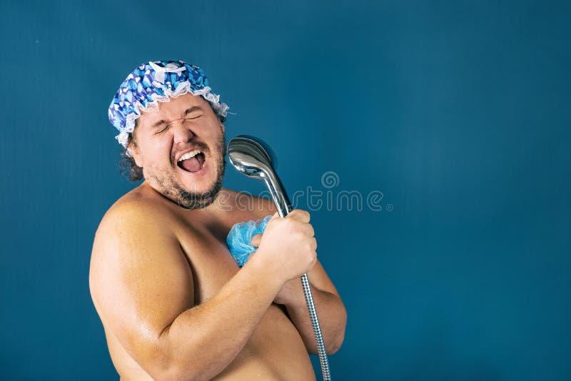 蓝色焰晕的滑稽的肥胖人在阵雨唱歌 免版税库存照片