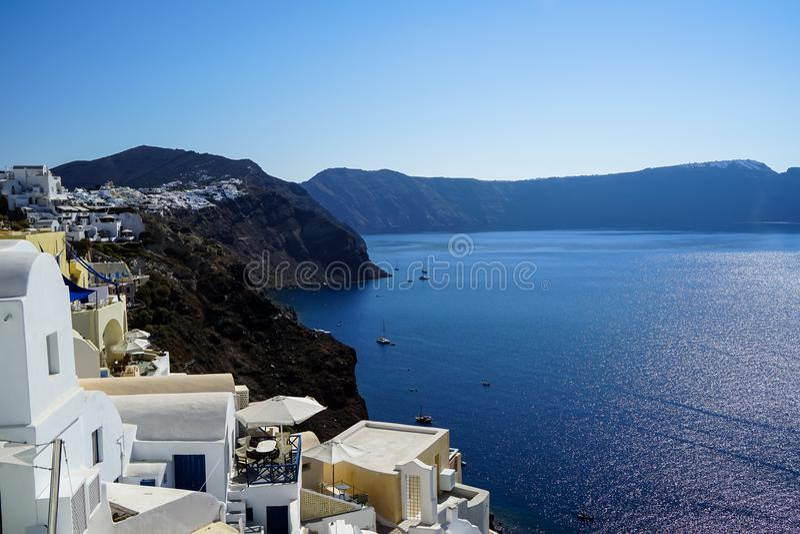 蓝色爱琴海全景,帆船和海洋浇灌从Oia村庄的反射有白色大厦都市风景的 库存照片