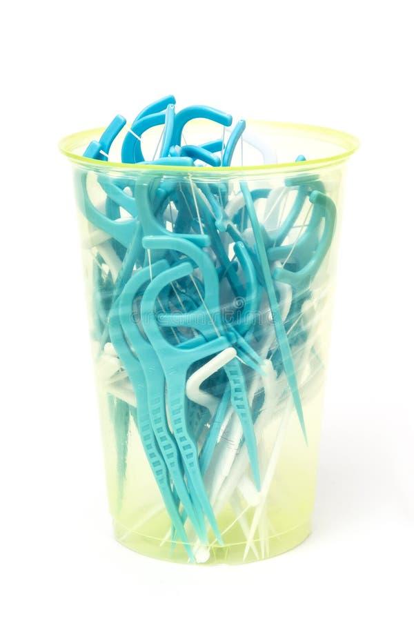 蓝色牙线在塑料杯子黏附在白色背景 免版税库存照片