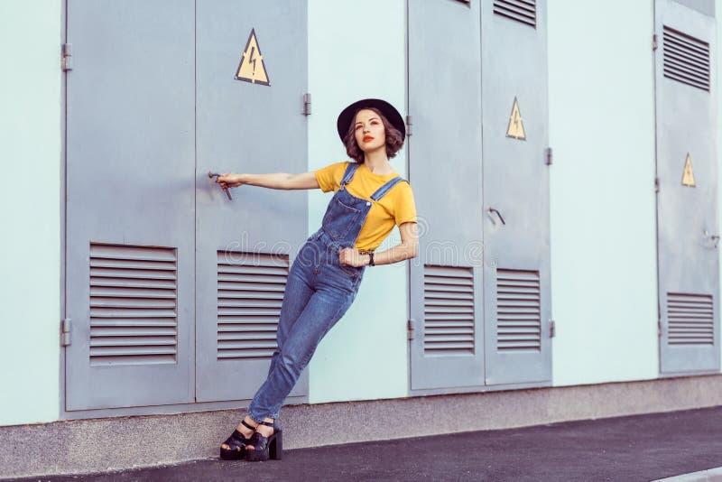 蓝色牛仔布总体和黄色T恤杉的年轻女人有黑帽会议肉欲查寻的,当摆在工厂厂房附近时 免版税图库摄影