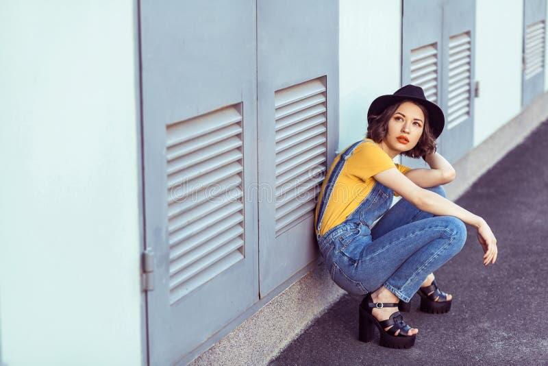 蓝色牛仔布总体和黄色T恤杉的年轻女人有黑帽会议肉欲查寻的,当摆在工厂厂房附近时 库存照片