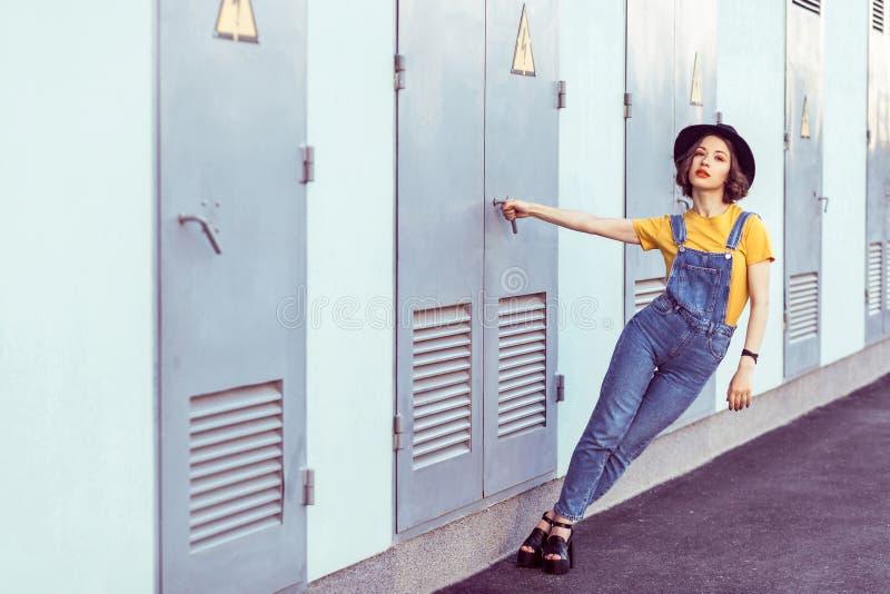 蓝色牛仔布总体和黄色T恤杉的年轻女人有黑帽会议肉欲的看的照相机的,当摆在工业附近时 免版税库存照片