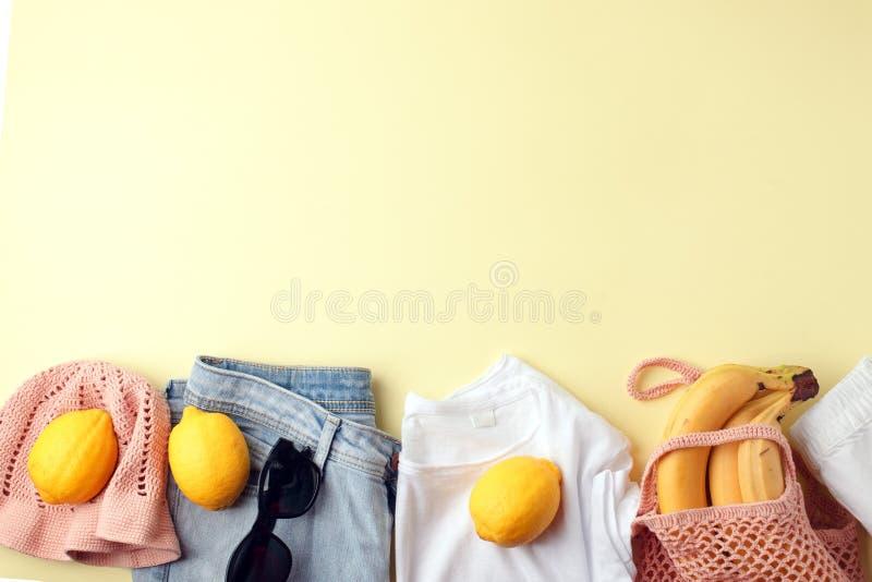 蓝色牛仔裤、白色衬衫、太阳镜、网兜和钩针编织帽子和柠檬在黄色背景 妇女的时髦的春天夏天 免版税库存图片