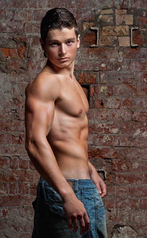 蓝色牛仔裤供以人员肌肉赤裸摆在的性感的年轻人 图库摄影