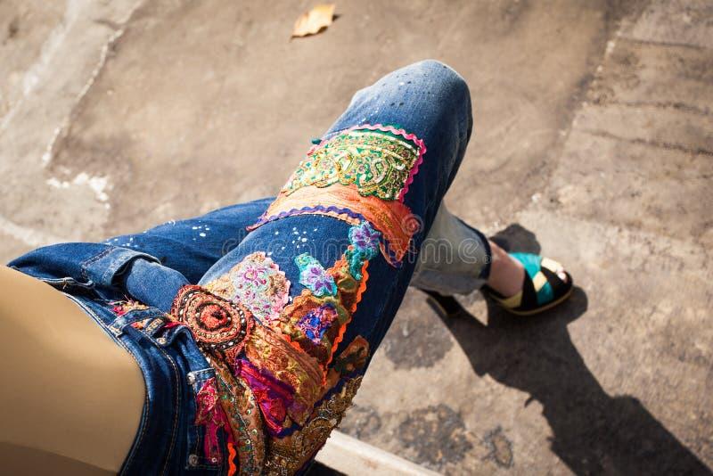 蓝色牛仔裤和高跟鞋的少妇在后院夏天烦恼 免版税库存图片