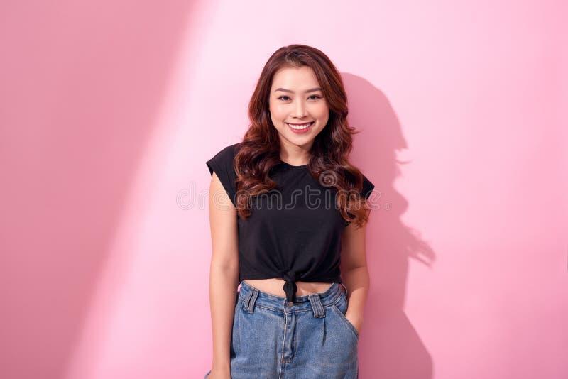 蓝色牛仔裤和黑衬衣摆在的美女,微笑在桃红色背景在演播室 免版税库存照片