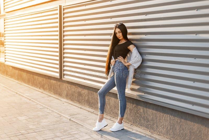 蓝色牛仔裤的俏丽的时兴的年轻女人在时髦的上面的白色运动鞋在有长发姿势的一件夏天夹克 免版税库存图片