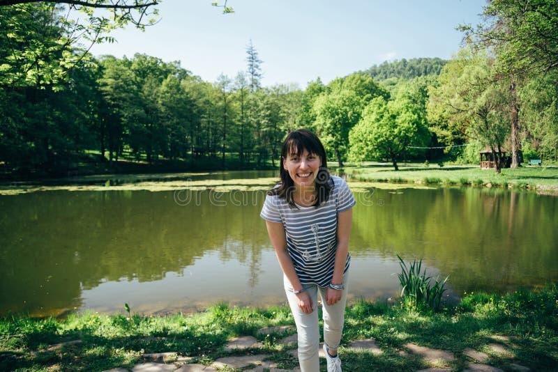 蓝色牛仔裤的旅游女孩和在森林包围的山湖的银行的镶边衬衣身分 库存图片