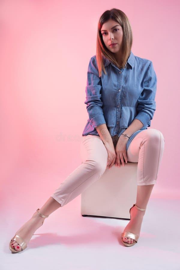 蓝色牛仔裤衬衣和高跟鞋的可爱的妇女在坐白色立方体凳子和摆在演播室的腿 免版税库存图片