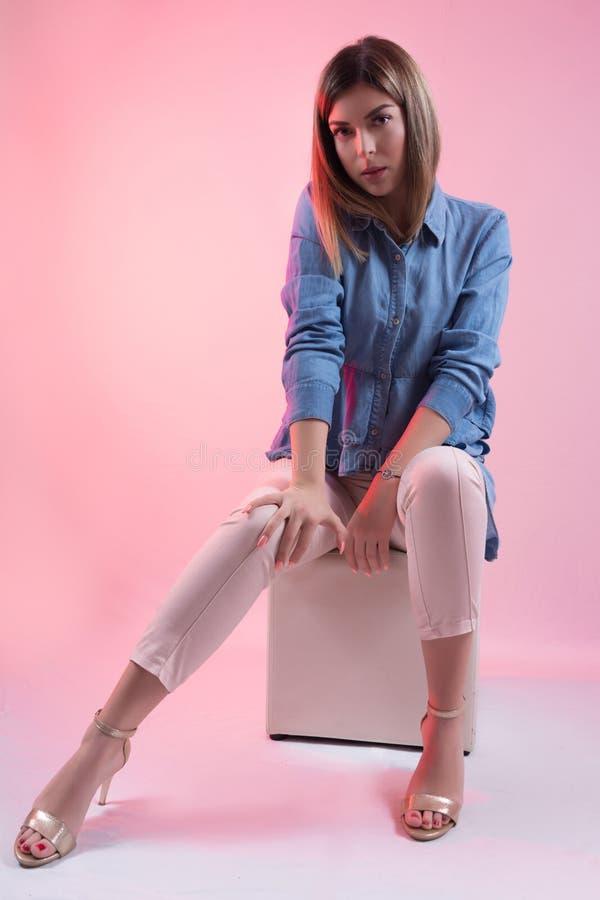 蓝色牛仔裤衬衣和高跟鞋的女性在腿坐白色立方体凳子和摆在演播室和隔绝在桃红色 免版税库存照片