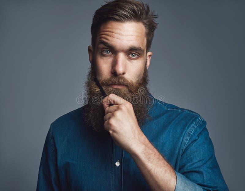 蓝色牛仔布的有胡子的人与严肃的表示 免版税库存照片